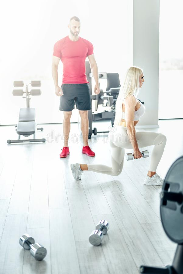 Blonde woman doing lunge exercise with personal trainer stock images