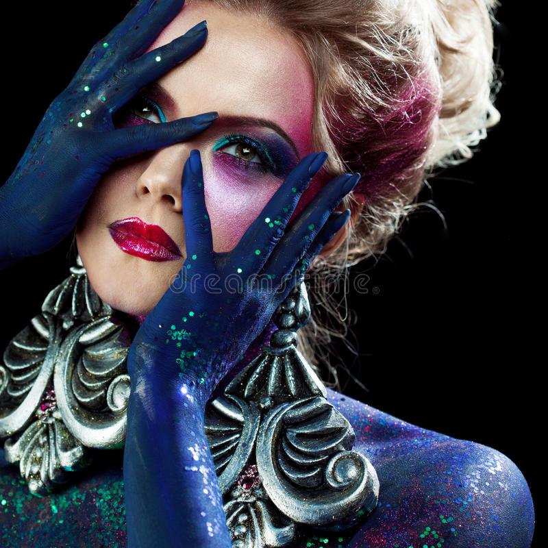 Young attractive blonde girl in bright art-makeup, high hair, body painting. Rhinestones and glitter. Young attractive blonde girl in a bright art-makeup, high royalty free stock images
