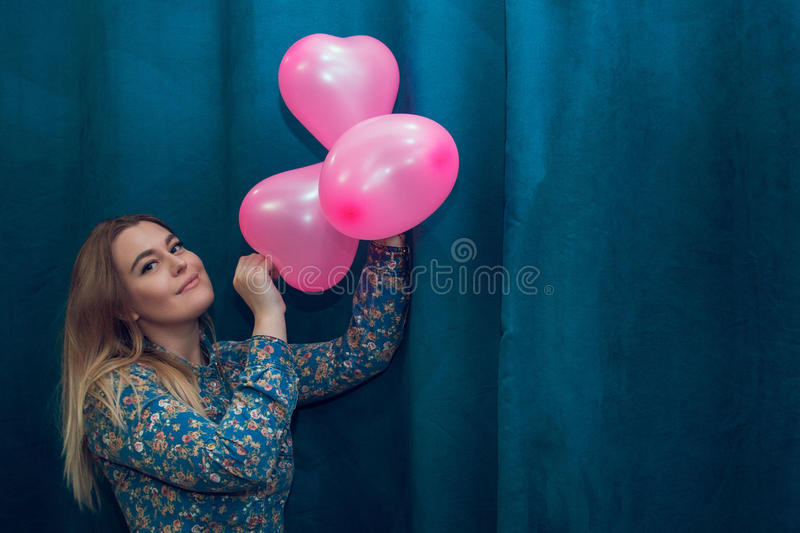 Young attractive blonde girl with pink heart shaped balloons. Young attractive blonde girl in a denim shirt with pink heart shaped balloons stock photography