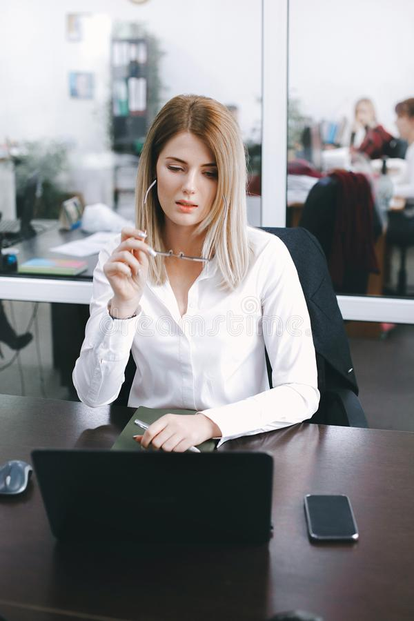 Young attractive blonde takes off glasses while working at table in office stock image