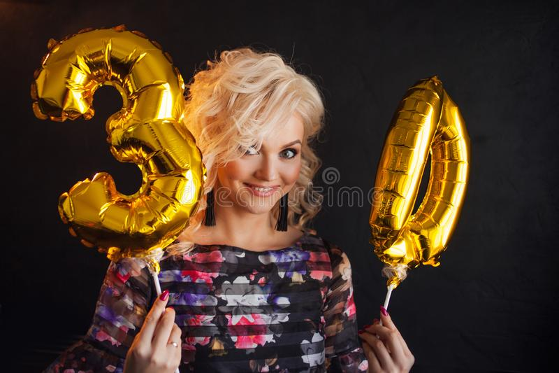 Young attractive blonde woman celebrates her 30th birthday. Beautiful cheerful blonde with Golden balloons. Birthday royalty free stock photo
