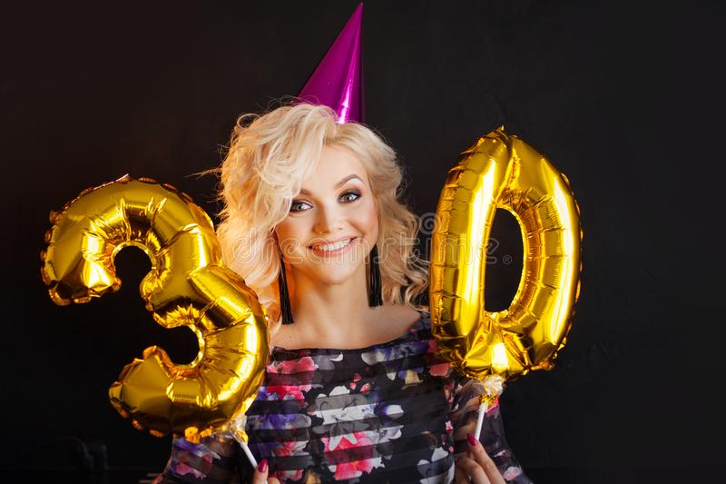 Young attractive blonde woman celebrates her 30th birthday. Beautiful cheerful blonde with Golden balloons. Birthday stock images