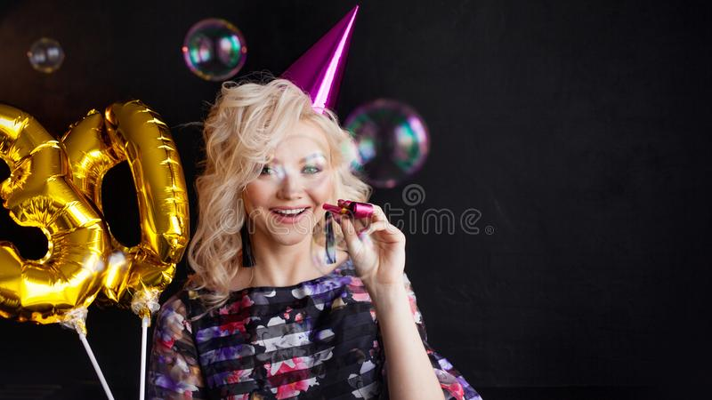Young attractive blonde woman celebrates her 30th birthday. Beautiful cheerful blonde with Golden balloons. Birthday stock photography