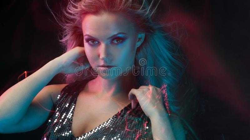 Young attractive blonde woman dancing in club, color light, motion effects. Black background, long exposure, Close-up portrait royalty free stock photography