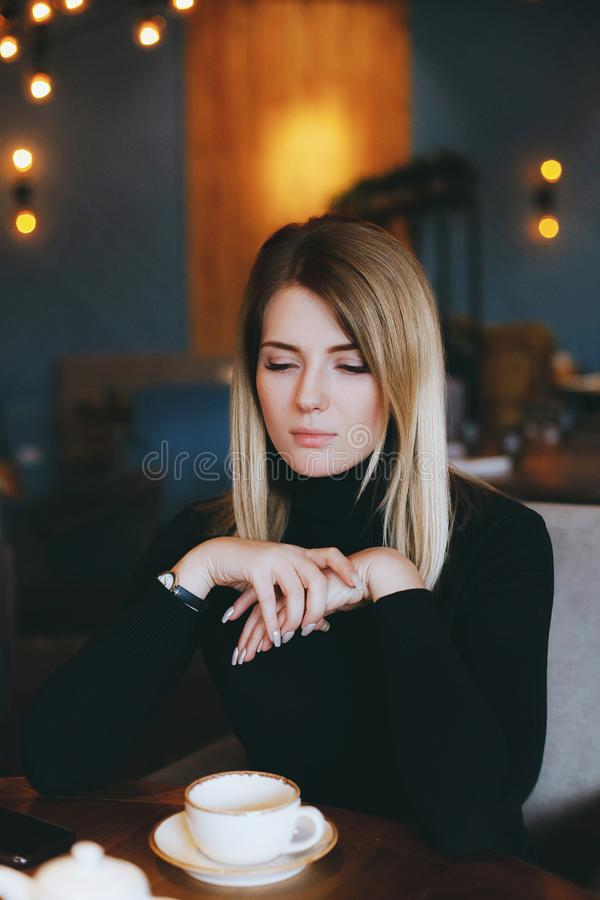 Young attractive blonde woman drinks tea in restaurant stock photo