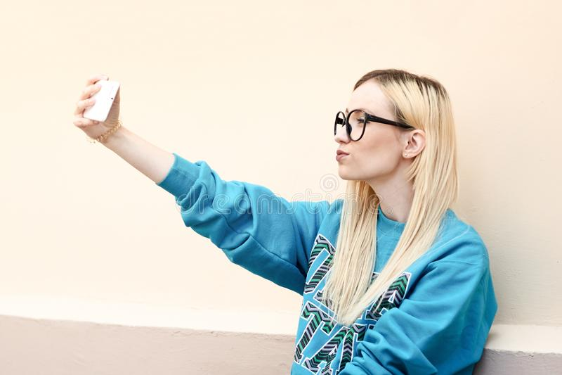 Young attractive blonde woman making selfie photo on smartphone. Pretty woman dressed in casual clothes talking in a video conference via mobile phone stock photo