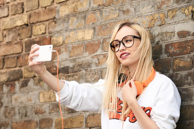 Young attractive blonde woman making selfie photo on smartphone. Pretty woman dressed in casual clothes talking in a video conference via mobile phone royalty free stock image