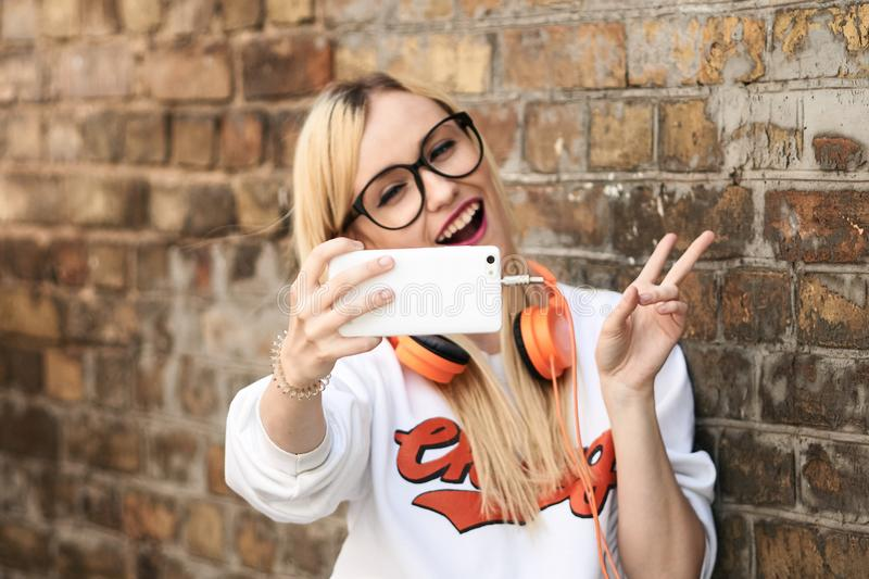 Young attractive blonde woman making selfie photo on smartphone. Pretty woman dressed in casual clothes talking in a video conference via mobile phone stock photos