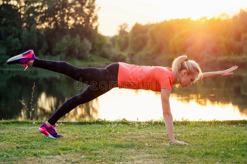 Young and attractive blonde woman in sportswear warm-up abdominal abc muscles press at the stadium on the grass lake. Background at sunset. sport active royalty free stock photos