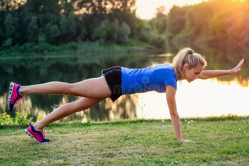 Young and attractive blonde woman in sportswear warm-up abdominal abc muscles press at the stadium on the grass lake. Background at sunset. sport active stock images