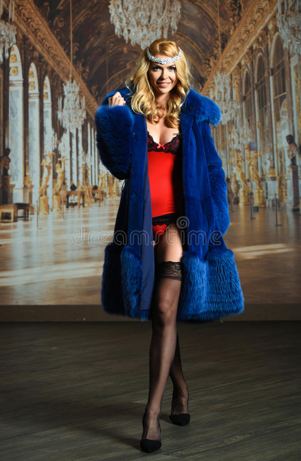 Young and attractive blonde woman wearing red lingerie, stockings and a fur coat. Young and attractive blonde woman wearing red lingerie, stockings and a fur stock images