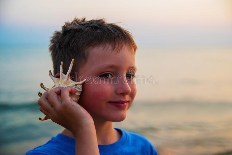Young attractive boy on a beach holding a sea shell against his ear and listening to the sound of waves smiling. During a vacation trip away stock photos