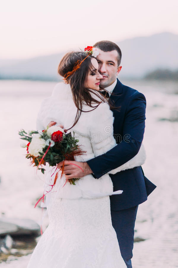 Young attractive bridal couple holding each other on pebble riverside with forest hills as background royalty free stock photography