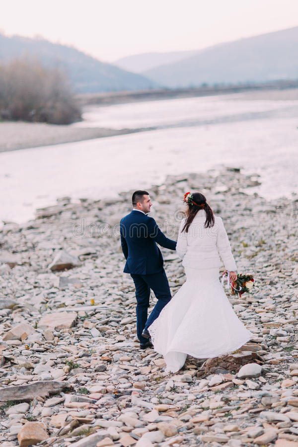 Young attractive bridal couple walking on pebble riverside with forest hills as background. Back view royalty free stock images
