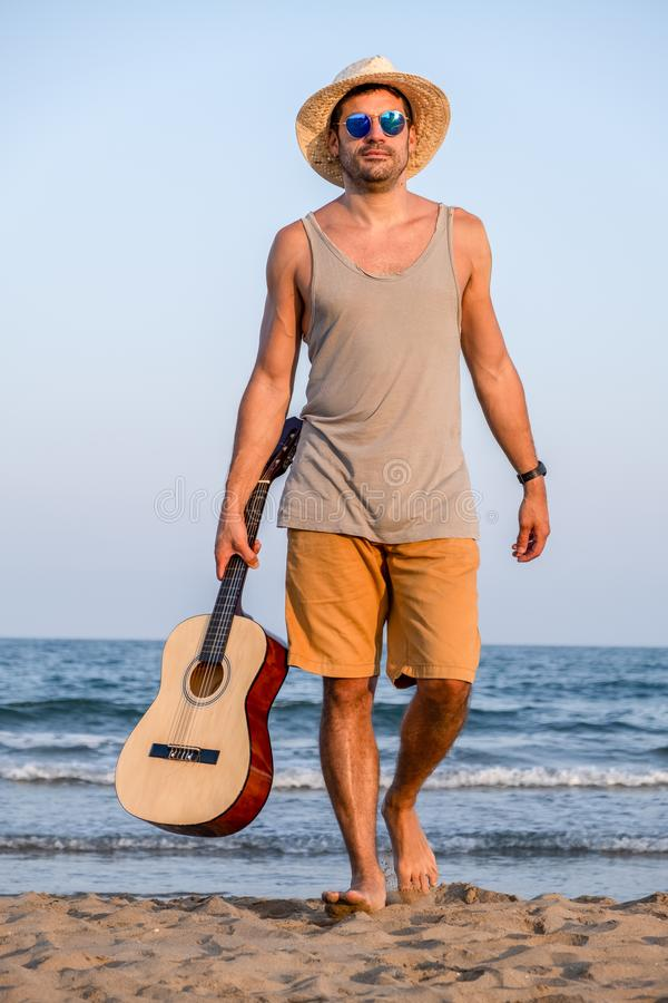 Brown boy dressed in summer form walks on the beach with a Spanish guitar stock image