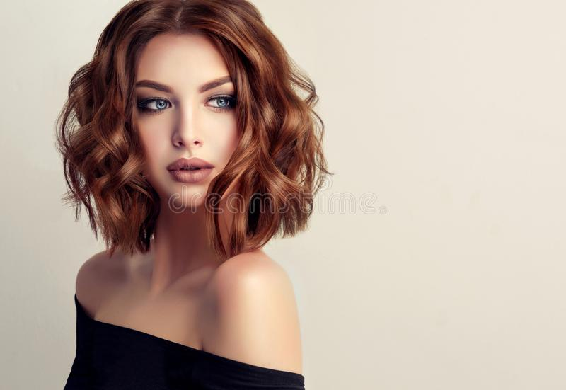 Young and attractive brown haired woman with modern, trendy and elegant hairstyle. Example of middle length,dense and curly hair.Gentle make up and long stock photos