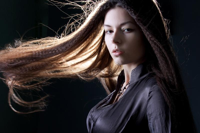 Young attractive brunette woman in dark. Beautiful young witch image for Halloween stock photo