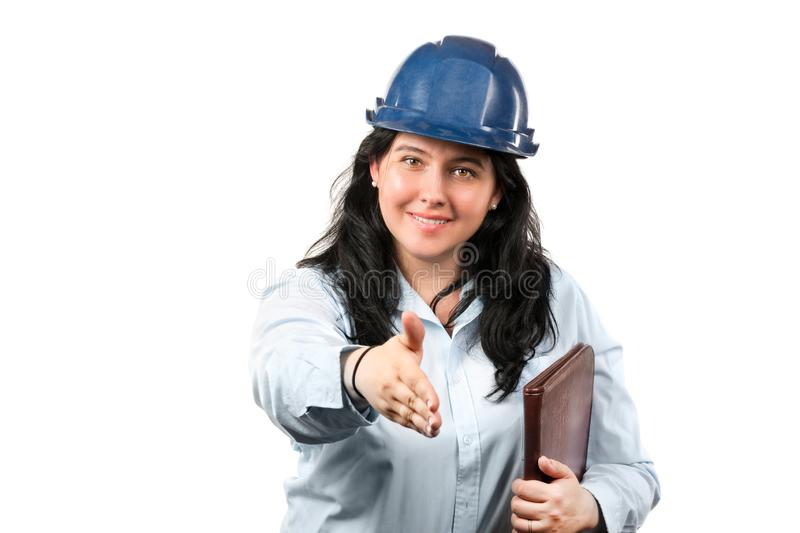 Young attractive brunette woman engineer or architect with blue safety hat pulling hand for handshake isolated on white background stock photos