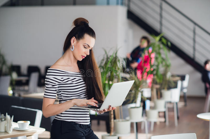 Young attractive brunette woman holding a laptop and typing, while looking at the screen. Young attractive brunette woman holding a laptop and typing, while stock image