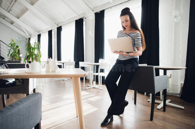 Young attractive brunette woman holding a laptop and typing, while looking at the screen. Young attractive brunette woman holding a laptop and typing, while royalty free stock photo
