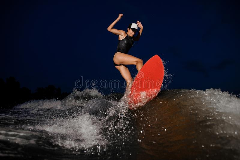 Young athletic woman jumping on the orange wakesurf in the night royalty free stock photo