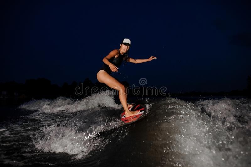 Young attractive woman riding on the orange wakesurf in the nigh royalty free stock photo