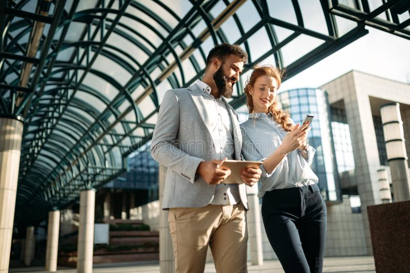 Young business couple walking outdoor near office building stock photography