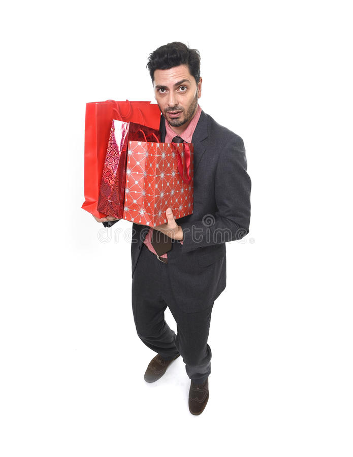 Young attractive business man in stress holding lot of shopping bags and help sign looking tired bored and worried. After expending too much money on gifts and royalty free stock image