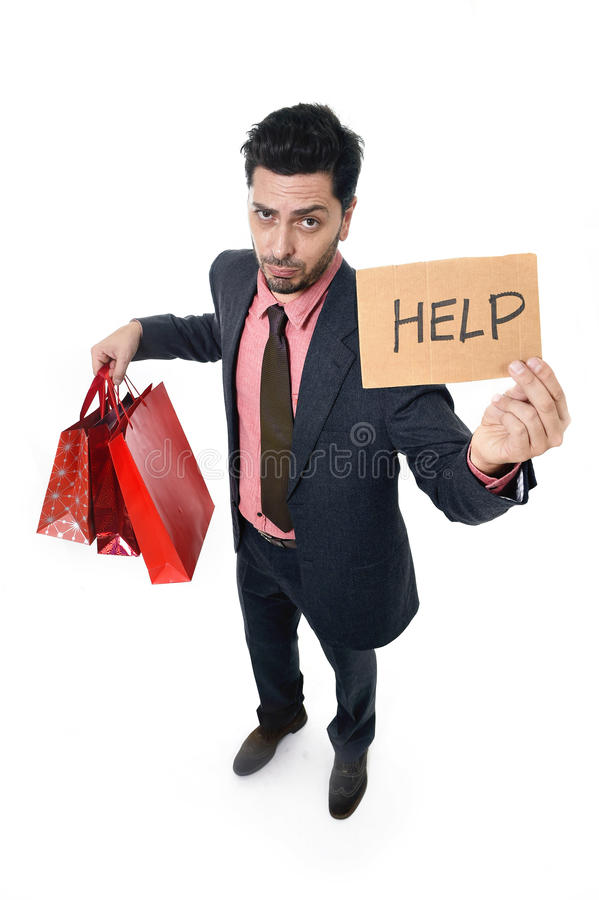 Young attractive business man in stress holding lot of shopping bags and help sign looking tired bored and worried. After expending too much money on gifts and royalty free stock photography