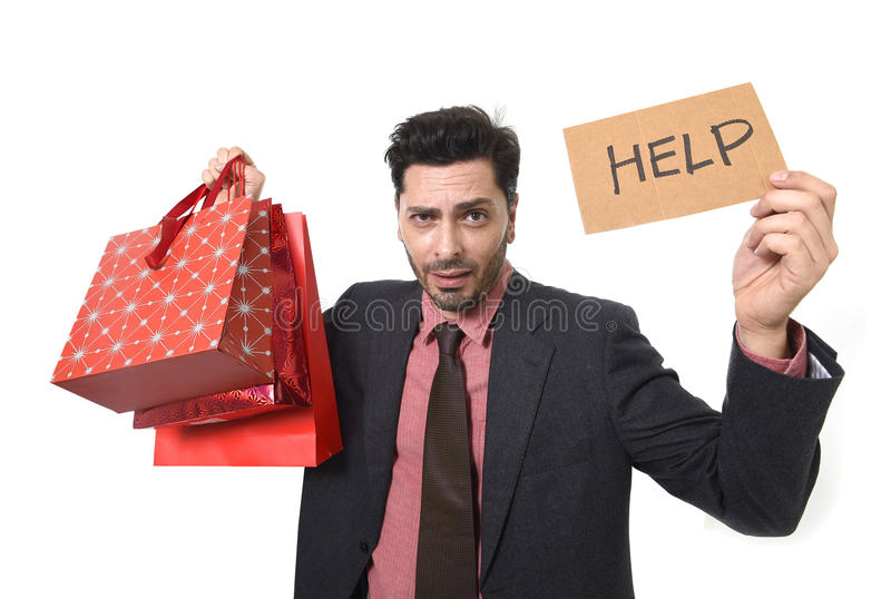 Young attractive business man in stress holding lot of shopping bags and help sign looking tired bored and worried. After expending too much money on gifts and royalty free stock photos
