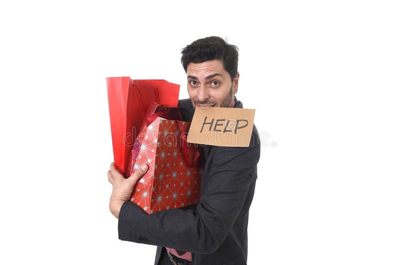 Young attractive business man in stress holding lot of shopping bags and showing help sign on his mouth looking tired bored and wo. Rried after expending too stock photo