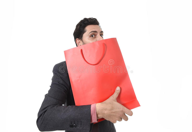 Young attractive business man in stress holding shopping bag looking greedy after buying bargain. Isolated on white background stock images