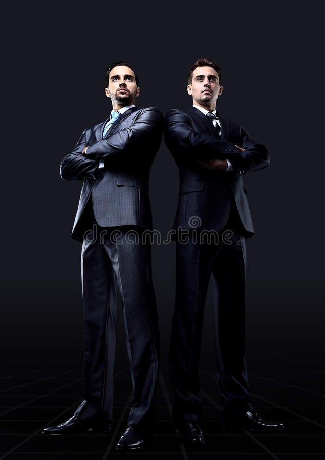 Young attractive business people. On a black background stock photography