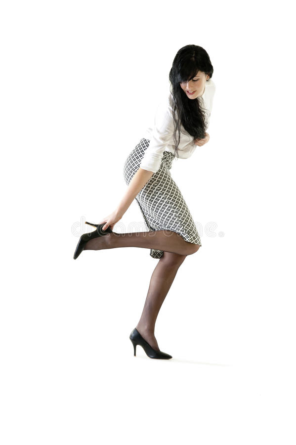 Young attractive business woman adjusting her shoe stock photo