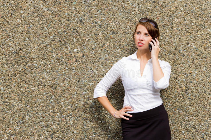 Young attractive business woman executive using her smart phone. A young attractive business woman executive using her smart phone to make a call royalty free stock photography