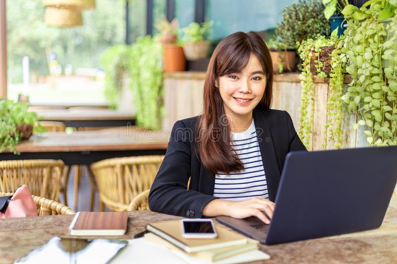 Young attractive business woman in her casual suit working on her computer at outdoor patio of her office, working mobile or young royalty free stock photography