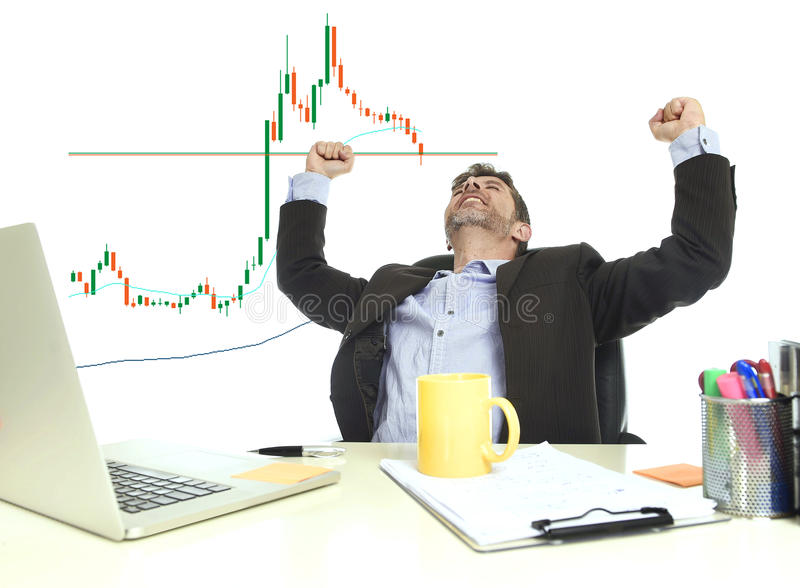Businessman crazy happy after winning forex or stocks trade at office computer desk celebrating. Young attractive businessman crazy happy after winning forex or royalty free stock photo