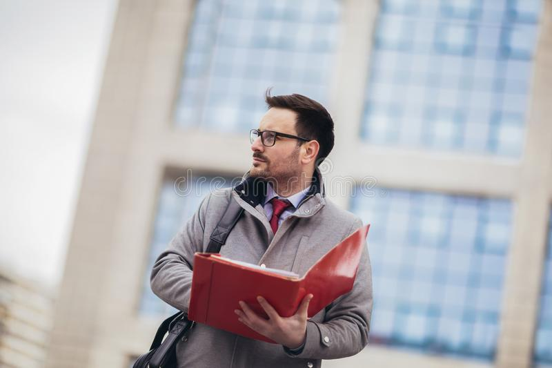 Attractive businessman holding documents, papers. Young concentrated man reading documents,  outdoors in urban area royalty free stock photos