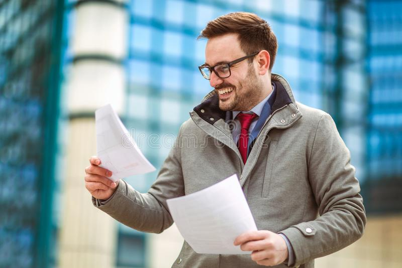 Young attractive businessman holding documents, papers. stock photo