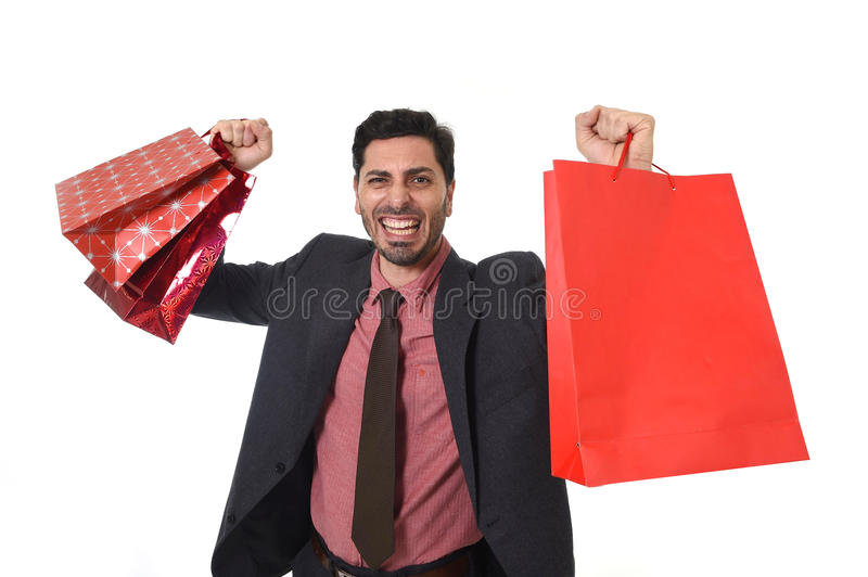 Young attractive businessman holding a lot of shopping bags in stress isolated on white background. Young attractive businessman holding a lot of shopping bags royalty free stock images