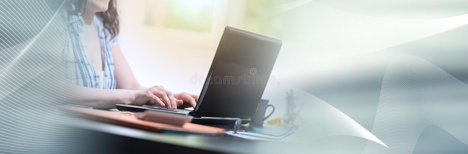 Young attractive businesswoman working on laptop, light effect; panoramic banner. Young attractive businesswoman working on laptop at office, light effect royalty free stock images