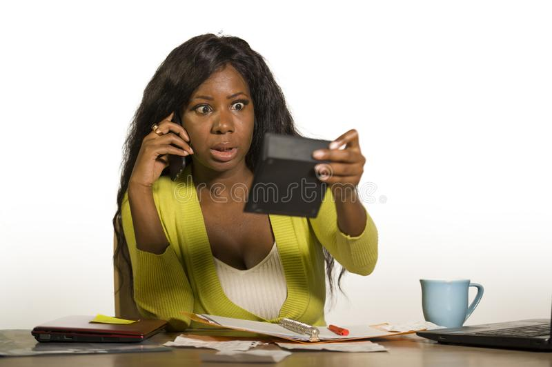 Young attractive and busy black afro American business woman working at home office computer desk talking on the phone holding cal. Culator accounting stressed royalty free stock images