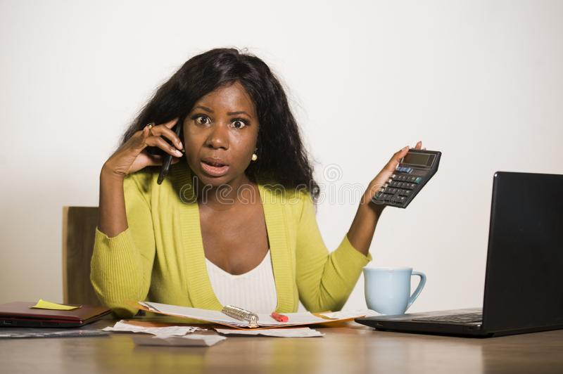 Young attractive and busy black afro American business woman working at home office computer desk talking on the phone holding cal royalty free stock photography