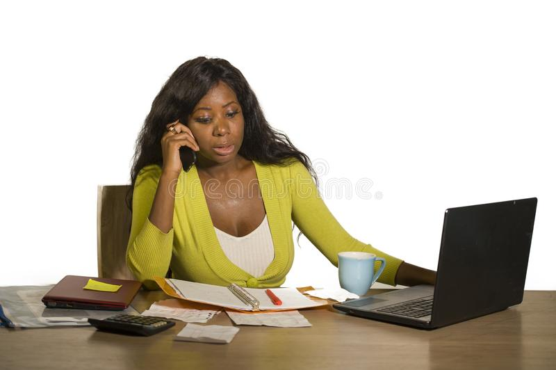 Young attractive and busy black afro American business woman working at home office computer desk talking on the phone stressed is royalty free stock photos