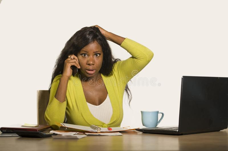 Young attractive and busy black afro American business woman working at home office computer desk talking on the phone stressed is. Olated on white background royalty free stock image