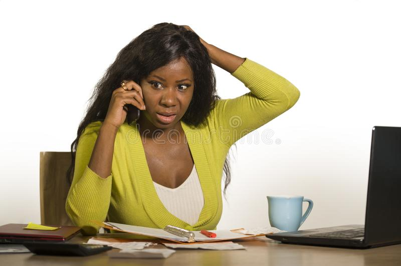 Young attractive and busy black afro American business woman working at home office computer desk talking on the phone stressed is. Olated on white background stock photo
