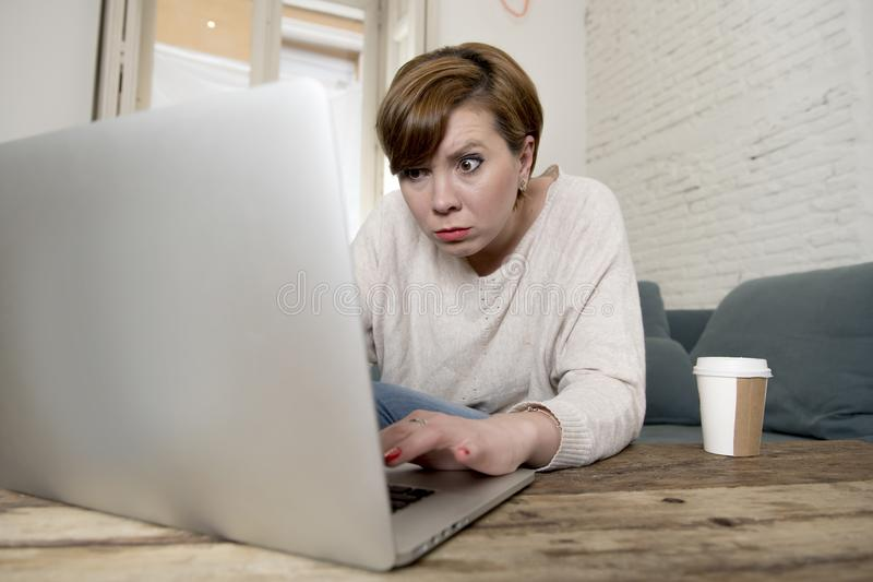 Young attractive and busy woman at home sofa couch doing some laptop computer work in stress looking worried in entrepreneur lifes. Tyle stock photo