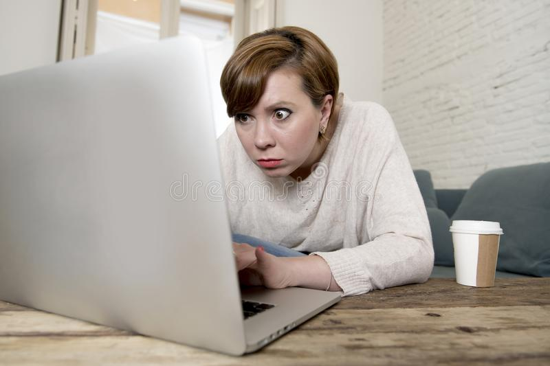 Young attractive and busy woman at home sofa couch doing some laptop computer work in stress looking worried in entrepreneur lifes stock photography