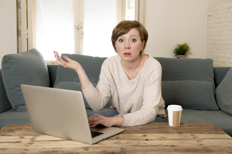 Young attractive and busy woman at home sofa couch doing some laptop computer work in stress looking worried in entrepreneur lifes stock photos