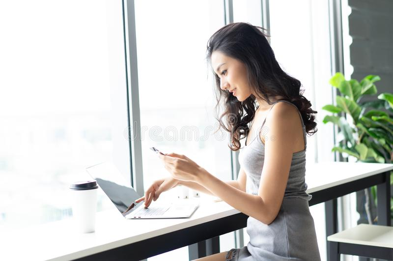 Young attractive caucasian Asian woman doing online shopping in coffee shop. Online shopping concept royalty free stock photos